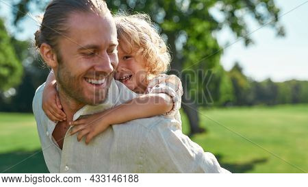Portrait Of Cute Little Boy Having Fun In The Park With His Father Giving Son Piggyback Ride On His