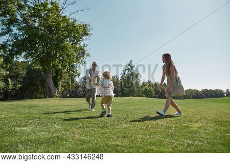 Active Parents Playing Together With Little Boy Child In Green Park On A Summer Day. Happy Family En