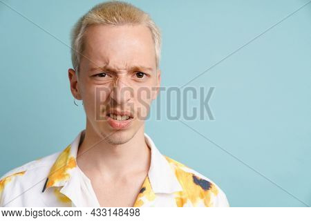 Young blonde man in shirt grimacing and looking at camera isolated over blue background