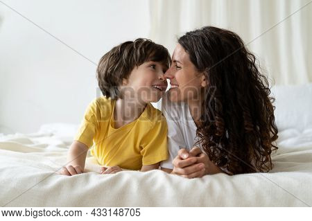 Mum And Kid Son Bonding Lying In Bed. Happy Smiling Mom And Small Child Enjoy Morning Together Tende