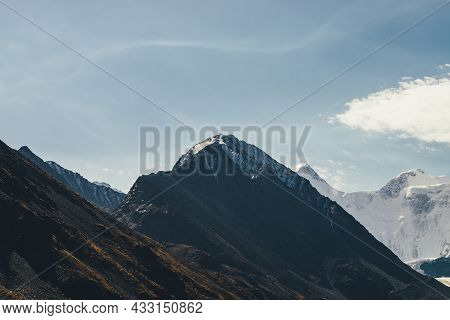 Atmospheric Alpine Landscape With High Mountain Silhouette With Snow On Peaked Top Under Cirrus Clou