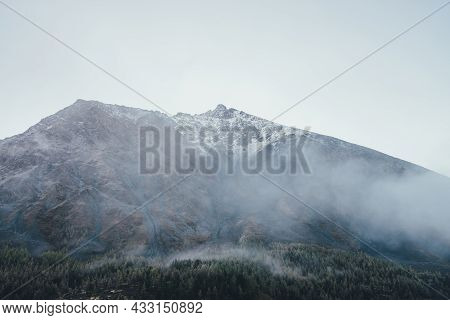 Wonderful View To Mountain Silhouette With Pointed Peak In Fog. Atmospheric Mountain Landscape With