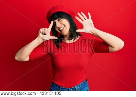 Young hispanic woman wearing french look with beret showing and pointing up with fingers number seven while smiling confident and happy.