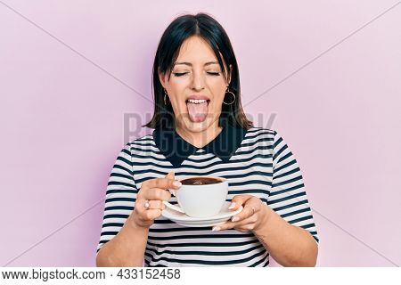 Young hispanic woman drinking a cup of coffee sticking tongue out happy with funny expression.
