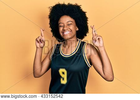 Young african american woman wearing basketball uniform gesturing finger crossed smiling with hope and eyes closed. luck and superstitious concept.