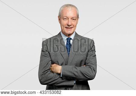 Cheerful senior businessman in a crossed arms gesture
