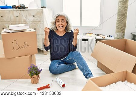 Middle age woman with grey hair sitting on the floor at new home screaming proud, celebrating victory and success very excited with raised arms