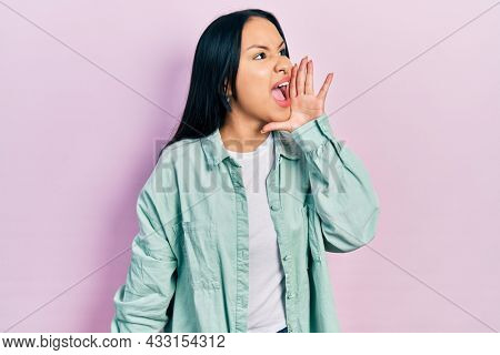 Beautiful hispanic woman with nose piercing wearing casual green jacket shouting and screaming loud to side with hand on mouth. communication concept.