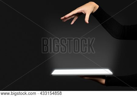 Hand presenting invisible hologram projecting from tablet advanced technology