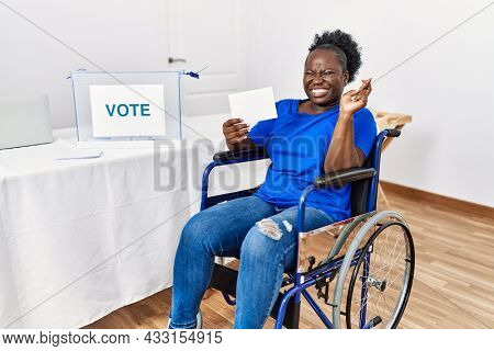 Young african woman sitting on wheelchair voting putting envelop in ballot box gesturing finger crossed smiling with hope and eyes closed. luck and superstitious concept.