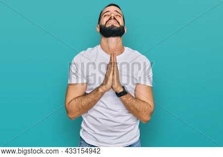 Young man with beard wearing casual white t shirt begging and praying with hands together with hope expression on face very emotional and worried. begging.