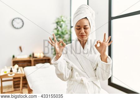 Young brunette woman wearing towel and bathrobe standing at beauty center relax and smiling with eyes closed doing meditation gesture with fingers. yoga concept.