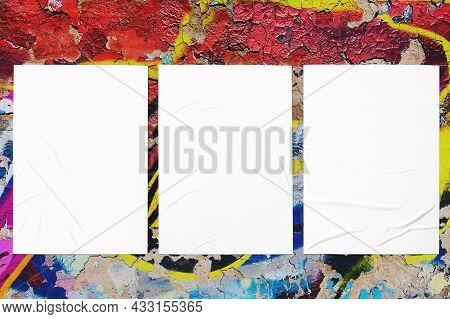Closeup Of Colorful Messy Painted Urban Wall Texture With Three Wrinkled Glued Poster Templates. Mod