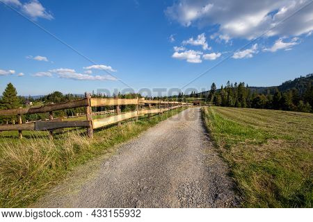 Dirt Road In The Silesian Beskids, Mountain Landscape With Path Along Wooden Fence