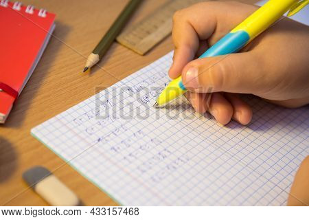 Pupils Hand Solves Math Examples With A Ballpoint Pen Close-up. A Schoolboy Performs A Task At The W
