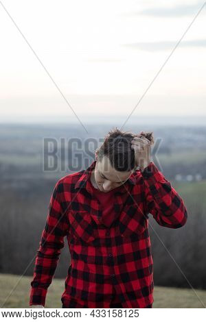 Candid Portrait Of A Man In His 20s Dressed In A Black And Red Checked Shirt Looking Into His Future