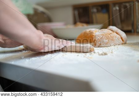 Low Angle View Of Female Hands Rolling A Dough On Flour Dusted Kitchen Counter To Make Italian Gnocc
