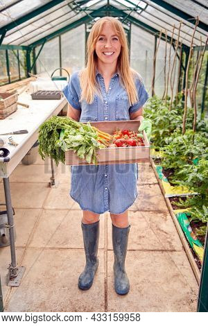 Full Length Portrait Of Woman Holding Box Of Home Grown Vegetables In Greenhouse
