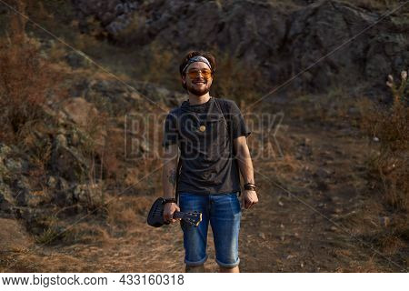 A Hippie Guy In Sunglasses Stands In A Clearing Near The Rocks Smiling And Looking Straight Into The