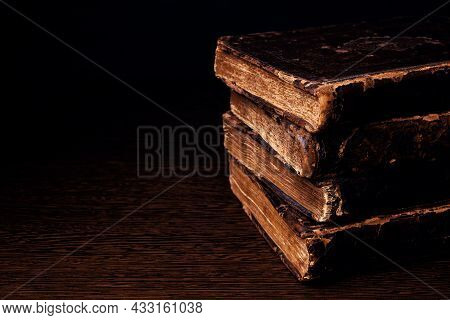 Stack Of Old Worn Shabby Jewish Book In Leather Binding In The Dark. Closeup. Selective Focus. Copy