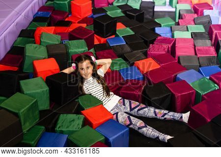 Portrait Little Cute Child Girl Playing And Jumping On Trampoline In Childrens Playroom, Indoors Pla