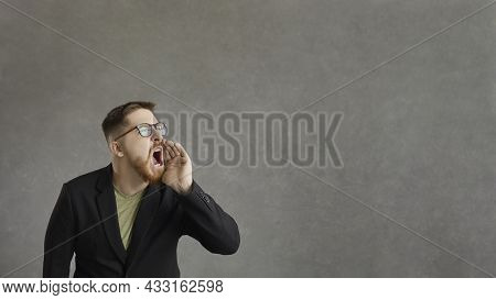 Active Man Who Shouts, Announcing Advertising Information Standing On A Gray Background.