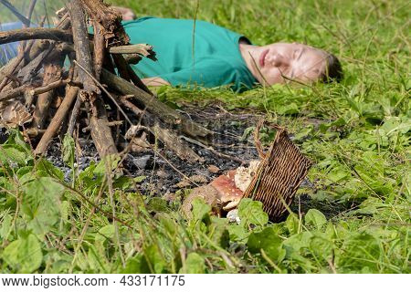 The Man Was Poisoned By Mushrooms Collected In The Forest.  Lies Unconscious Near The Fire, Nearby A