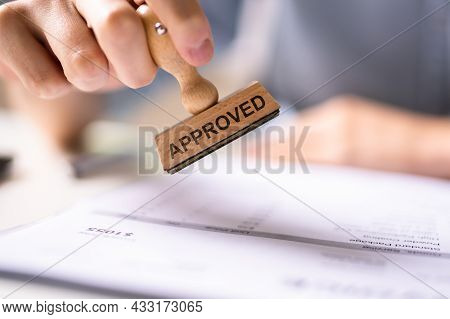 Hand Stamping With Approved Stamp On Document At Desk