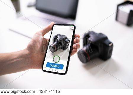 Man Uploading Mobile Phone Photo Of Camera Online