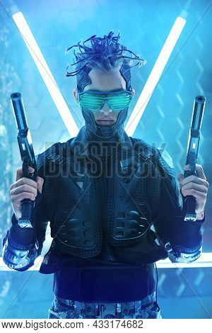 Warrior of the future. A brave cyberpunk warrior in protective uniform stands on alert with weapons in his hands in neon light. Game, virtual reality.