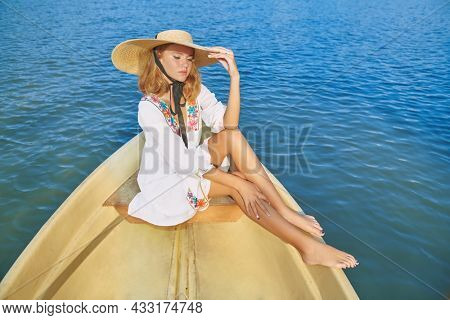 Summer vacation. Beautiful tanned blonde girl in a light white dress and a wide-brimmed straw hat on a sea trip. Summer fashion and beauty.