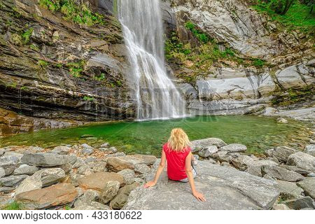 Woman Sitting By The Water Of Great Waterfall Of Bignasco, Valle Maggia, Intersection Point Between