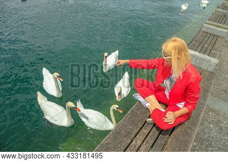Zurich Lake In Zurich City With Blonde Tourist Woman With White Swans In Turquoise Waters. Lakefront
