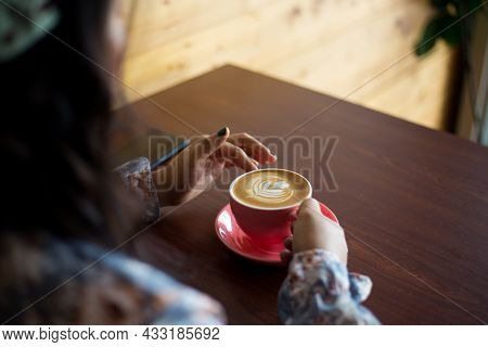 Horizontal Closeup Shot Of A Young Woman Sitting In A Café Holding A Cup Of Latte. Indoor Lifestyle