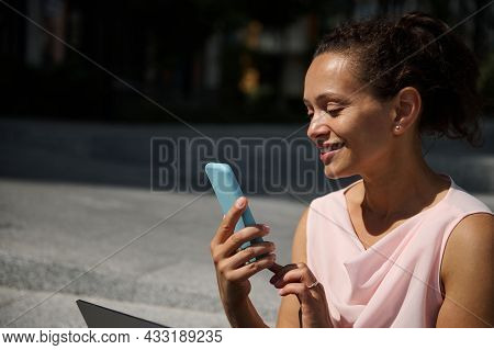 Attractive Smiling African American Woman Swiping On Smartphone. Attractive Cheerful Mixed Race Woma