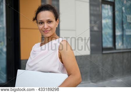 Close-up Business Portrait Of Mixed Race Attractive Woman In Casual Attire Holding Laptop Computer,