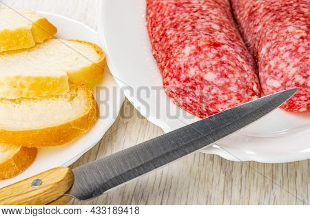 Slices Of Wheat Bread In White Plate, Slices Of Sausage Salami In White Dish, Kitchen Knife On Woode