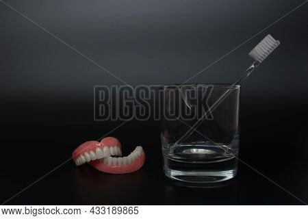 Full Removable Plastic Denture Of The Jaws. A Set Of Dentures On A Black Background. Two Acrylic Den