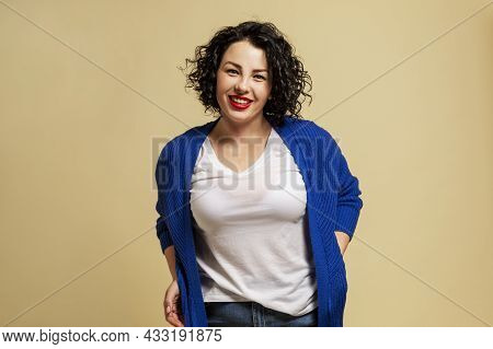 Positive Plump Girl. Young Beautiful Brunette In A Blue Sweater And Jeans Laughs. Yellow Background.