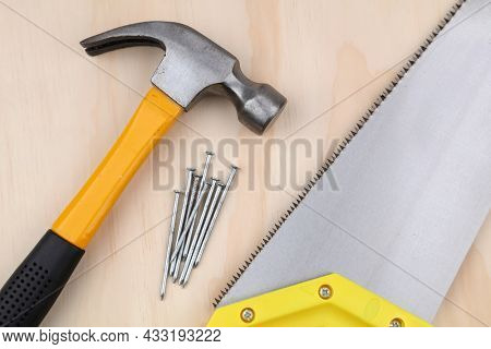 Hammer, nails and saw on wood