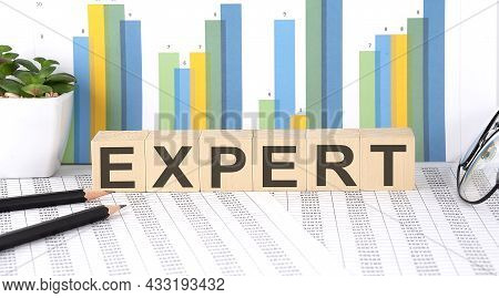 Expert Word Written On Wood Block With Chart, Glasses And Pencils