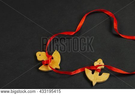 Two Wooden Anchors Tied With Red Ribbon. Anchor Figures On Black Surface. Nautical Theme. Selective