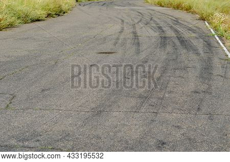 Gray Asphalt With Black Tire Tracks. An Old Country Road With Cracks. Green Grass On The Side Of The