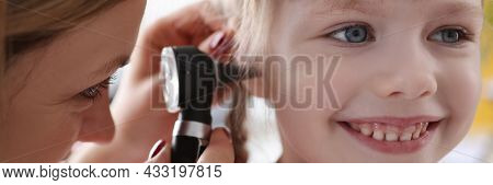 Ent Doctor Examining Sore Ear Of Small Child Using Otoscope