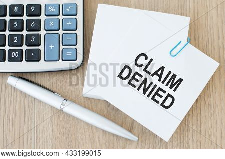 A White Card With The Inscription Claim Denied On The Table Next To A Calculator And A Pen