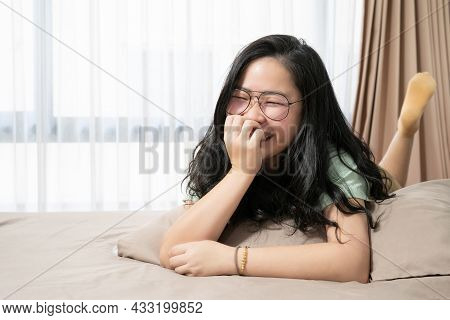 Beautiful Glasses Asian Woman Feels Embarrassed And Smiles To The Camera And Lays Down On Her Bed  I