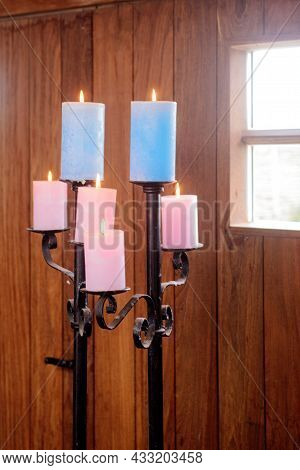 Standaard With Colored Candles In Wooden Cabin With Daylight Shinning Through The Windows