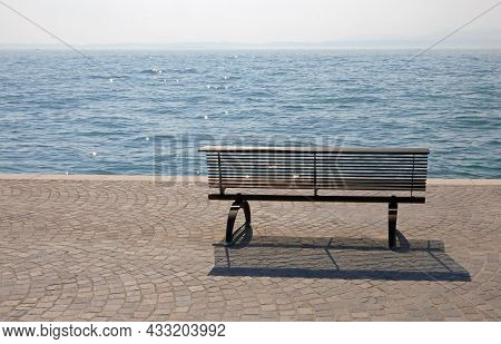 Lonely Bench On The Shore With The Placid Water Symbol Of Tranquility