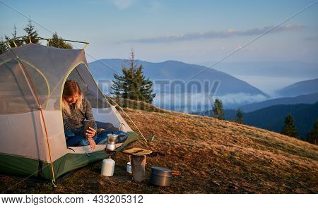 Woman Traveler Sitting In Camp Tent And Taking Photo Of Tourist Gas Burner And Kettle. Female Hiker
