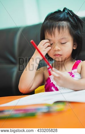 Vertical Image. Cute Girl Is Scratching Her Face Due To Itching As She Sits Painting On The Table.
